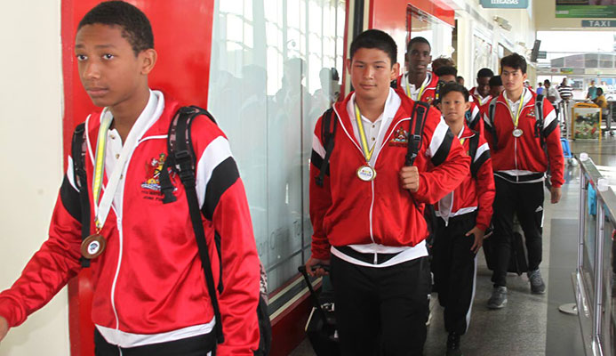 In this file photo, members of the TT water polo boys Under-15 team arrive at the Piarco International Airport, on July 8, after winning gold in CCCAN water polo, in Barbados.
