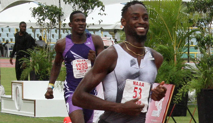 Jereem Richards eases up at the finish -line to win the men's 200 metres title from the 2018 winner and Abilene Wildcats clubmate Kyle Greaux at the NGC/NAAATT National Open Championships at the Hasely Crawford Stadium, Mucurapo, yesterday. Richards clocked 20-14 seconds and Greaux 2018 with Akanni Hislop of Kaizen Panthers third in 20.68 seconds.